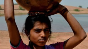 Young girl carrying water from a nearby source